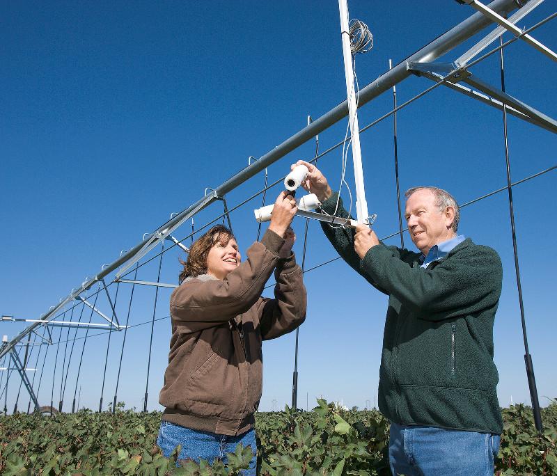 Susan O'Shaughnessy et Nolan Clark, ingénieurs agricoles du Service de recherche agricole de USDA, ajustent le champ de vision des thermomètres infrarouges sans fil montés sur un système d'irrigation à pivot central. Les capteurs sans fil sont utilisés pour mesurer la température de la canopée des cultures pour des indications de stress hydrique. (credits: U.S. Department of Agriculture (USDA) / Flickr Creative Commons Attribution 2.0 Generic (CC BY 2.0))