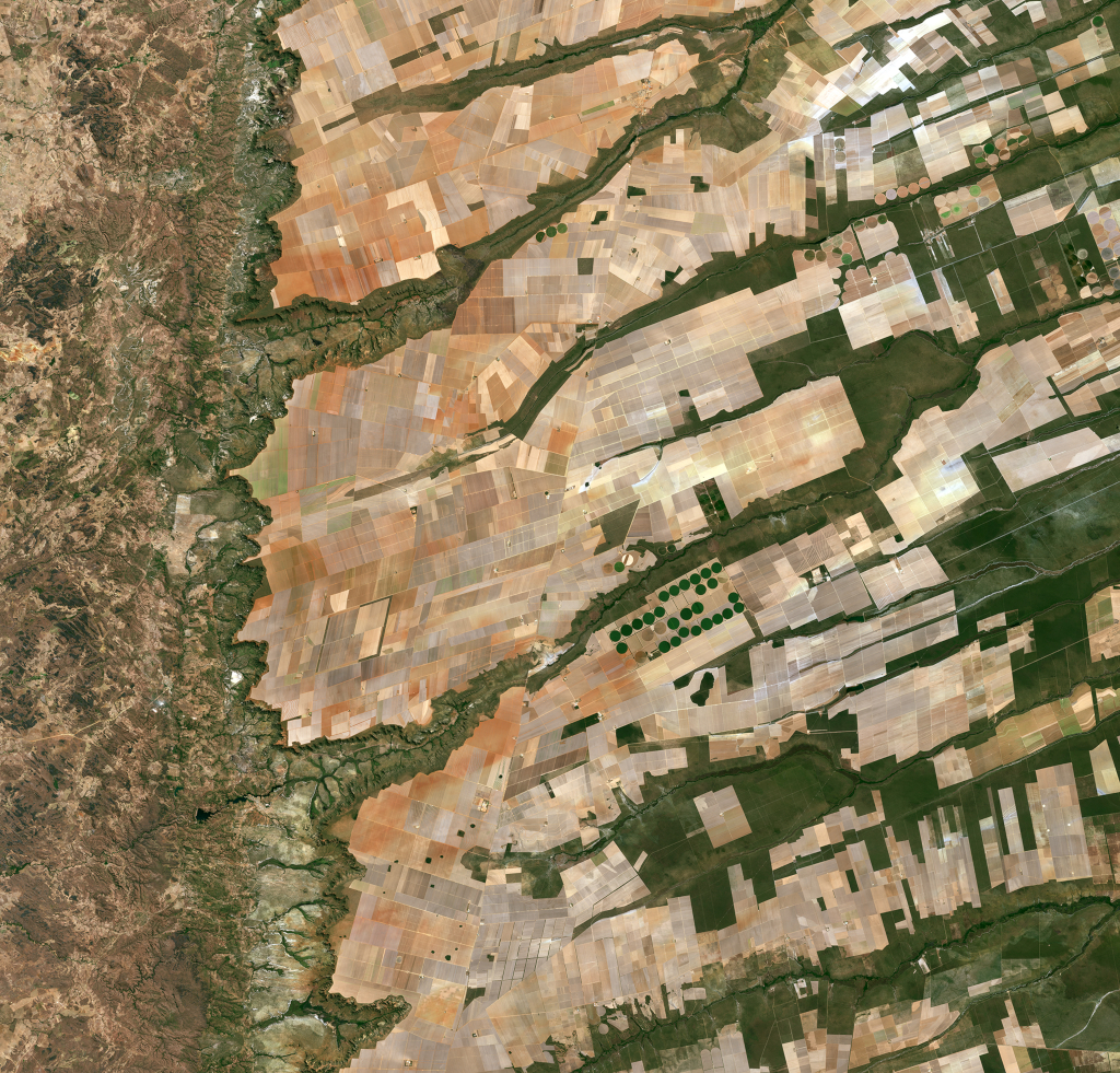 Sentinel-2A nous emmène dans le centre-est du Brésil, plus précisément là où se rencontrent les États de Bahia, Tocantins et Goiás. Nous pouvons voir ici un grand plateau plat, couvert de champs bénéficiant de sols riches et d'une abondance apparente d'eau, avant de tomber dans une vallée verdoyante et vallonnée (à gauche). Une caractéristique distinctive de cette image est les cercles - principalement au centre. Ces formes ont été créées par un système d'irrigation à pivot central, dans lequel une longue conduite d'eau tourne autour d'un puits au centre de chaque parcelle. Les différentes couleurs montrent différents types de cultures ou différents stades de croissance. (Copyright contains modified Copernicus Sentinel data (2016), processed by ESA ,CC BY-SA 3.0 IGO)