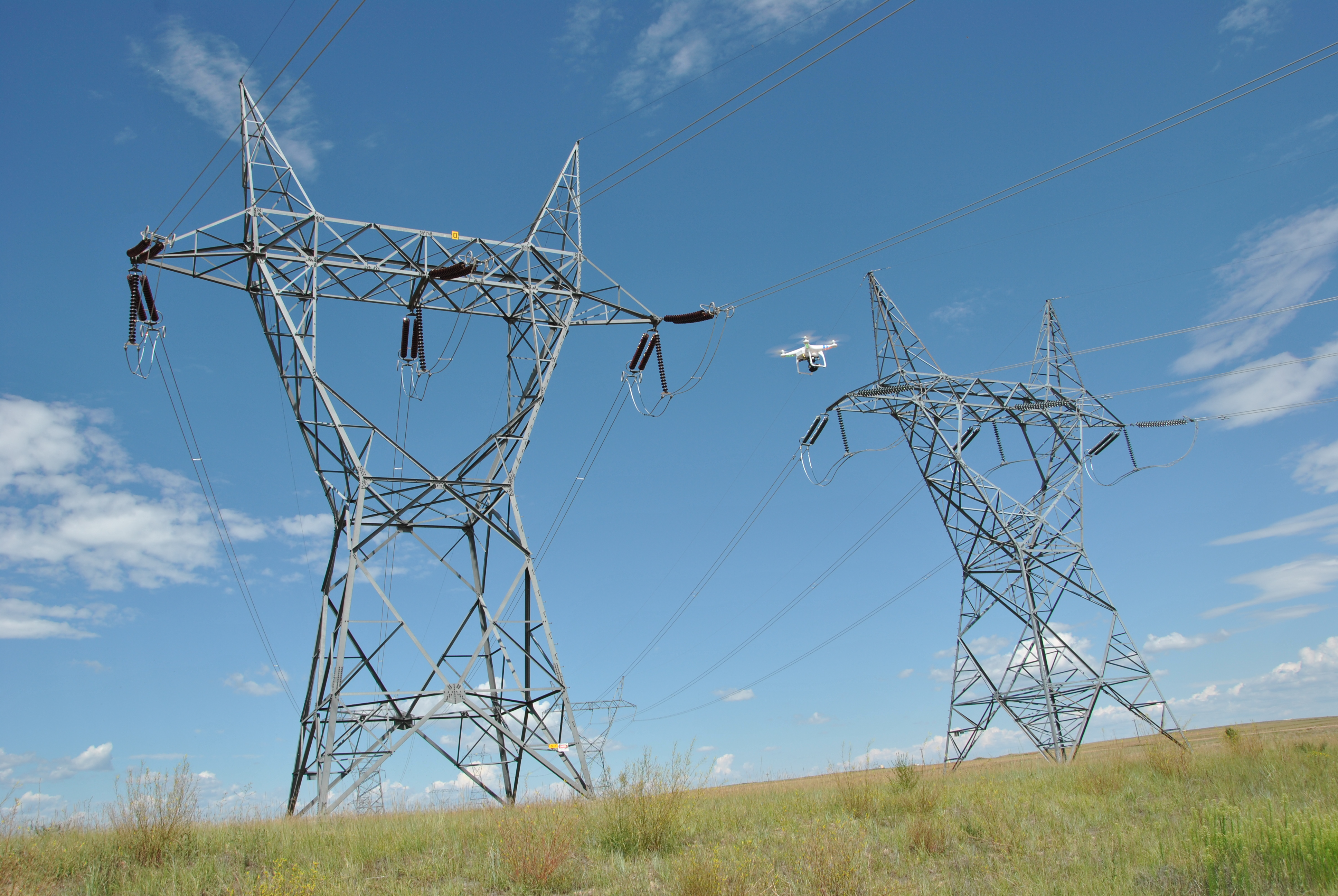 A small aerial remote control device flies in front of Western's Ault-to-Craig 345-kilovolt transmission line outside Ault Substation in Colorado, Aug. 6, 2014. The equipment has flown as close as two feet to energized lines without impact. (credits: Lisa Meiman / Western Area Power / Flickr Creative Commons Attribution 2.0 Generic (CC BY 2.0))
