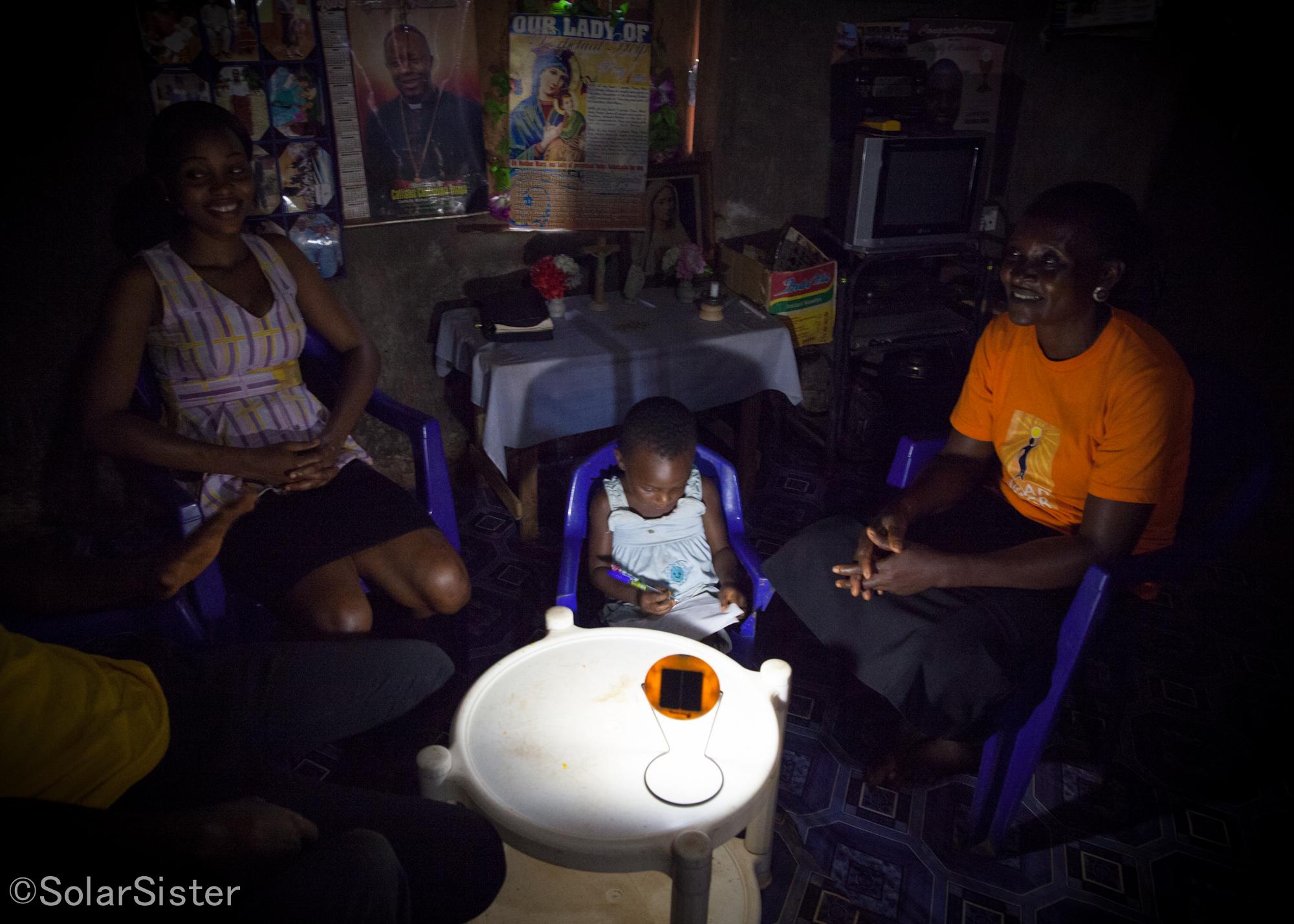 Eucharia discute avec ses voisins pendant que sa petite fille dessine à la lumière d'une lampe solaire (crédits: Solar Sister / Flickr Creative Commons Attribution-NonCommercial-NoDerivs 2.0 Generic (CC BY-NC-ND 2.0))